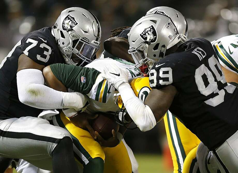 Green Bay Packers quarterback Brett Hundley, center, is sacked by Oakland Raiders defensive tackle Maurice Hurst (73) and defensive end Fadol Brown, obscured, during the first half of an NFL preseason football game in Oakland, Calif., Friday, Aug. 24, 2018. At right is Raiders defensive end Arden Key (99). (AP Photo/D. Ross Cameron) Photo: D. Ross Cameron / Associated Press