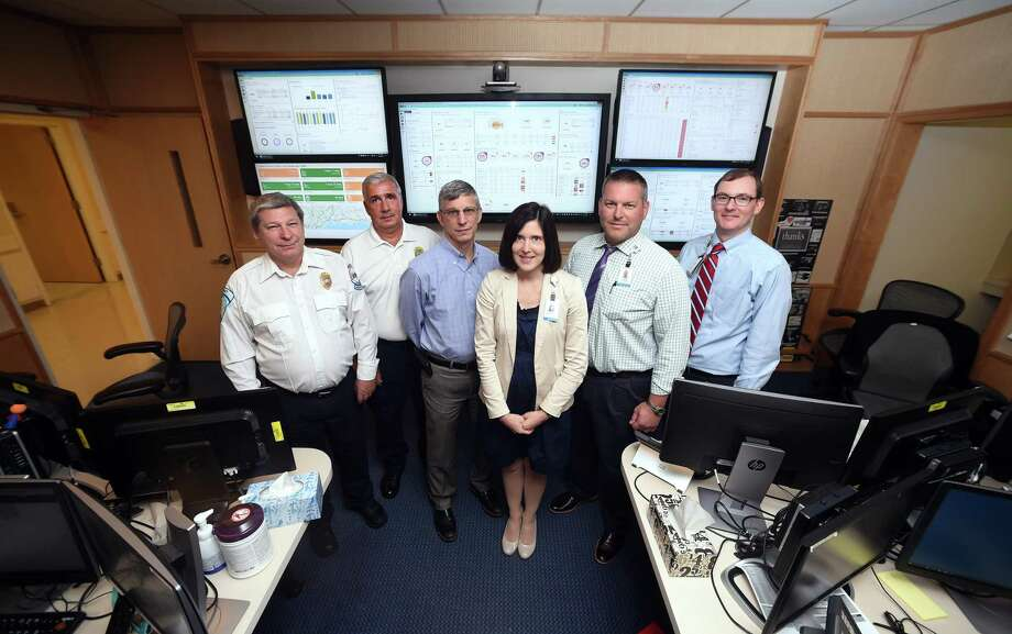From left, Tim Craven, operations manager for American Medical Response; Rick Fontana, New Haven's director of emergency operations; Dr. Andy Ulrich, operations director for the Department of Emergency Medicine; Maribeth Cabie, director of clinical operations for Yale New Haven Hospital; Tom Saxa, patient service manager for the Emergency Department, and Dr. Robert Fogerty, director of bed resources for Yale New Haven Hospital, are photographed in front of the real-time capacity dashboards at the Capacity Coordination Center at Yale New Haven Hospital on August 13. Photo: Arnold Gold / Hearst Connecticut Media / New Haven Register