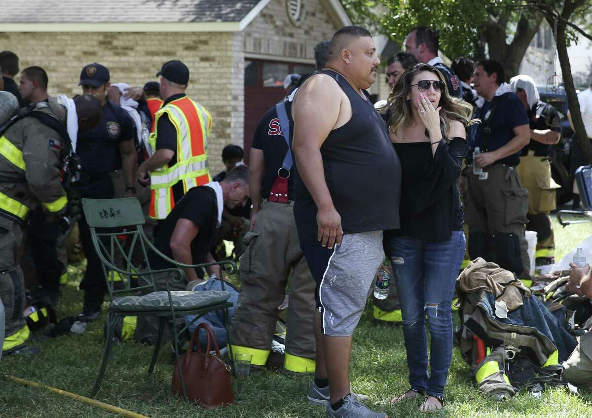 A man and a woman wqtch as San Antonio firefighters finish with a structure fire involving two houses on the 4700 block of Desert Poppy, Sunday, August 26, 2018. Over 30 units responded the the fire.