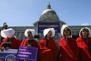 "Women in ""Handmaid's Tale"" costumes make a statement at the Unite for Justice rally in San Francisco."