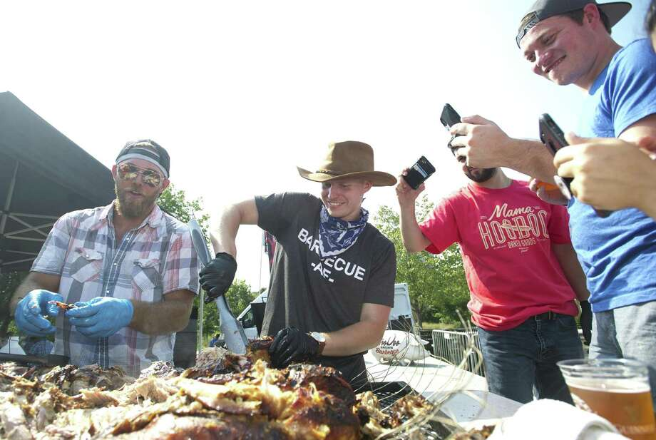 Above, Hoodoo Brown BBQ employees Kevin O'Connor, center, and Travis Tiger pull about a roast pig in front of a large crowd during a live demonstration at the second annual Hey Stamford! Food Fest at Mill River Park in downtown Stamford on Sunday. Hoodoo Brown BBQ is located in Ridgefield. At right, Casey Baker, 9, of Stamford, licks the side of a waffle cone ice cream. Photo: Michael Cummo / Hearst Connecticut Media / Stamford Advocate