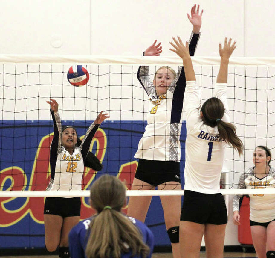 CM's Sydney Henke (middle) rises above the net to fake an attack that draws the block of Brussels' Toni Odelehr (1) while Eagles freshman DS Ella Middleton pushes a shot from the back during pool play last week at the Roxana Tourney. Photo: Greg Shashack / The Telegraph