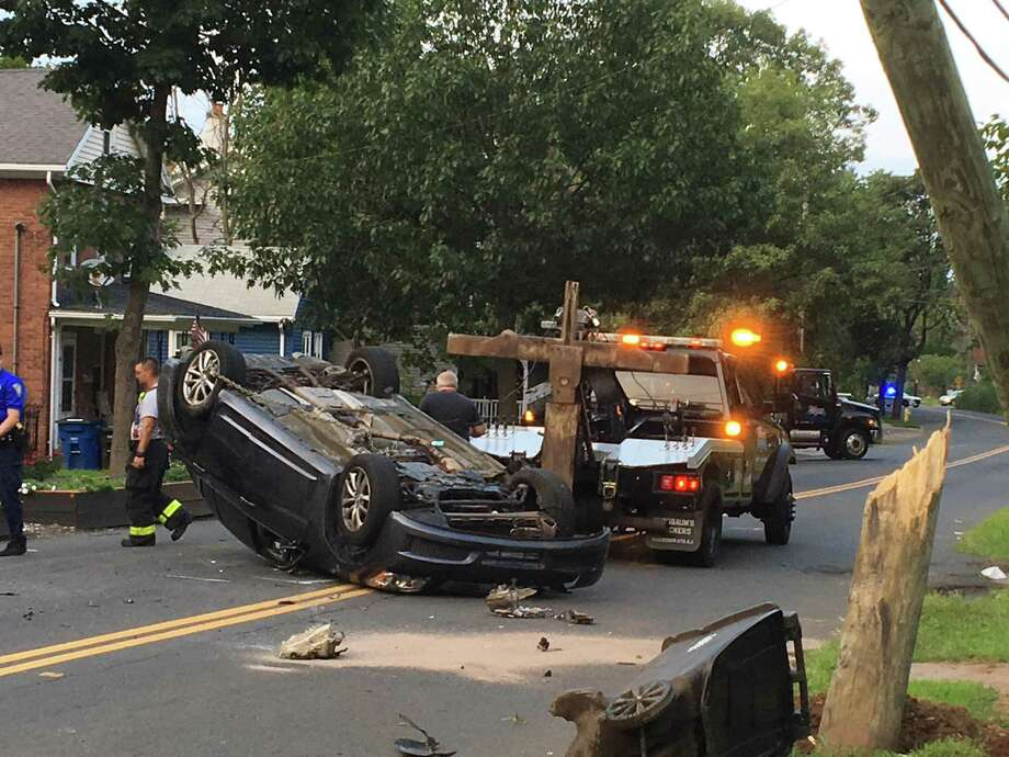 A tow truck driver works to right a flipped vehicle on Quinnipiac Avenue on Sunday, Aug. 26, 2018, as firefighters watch. A woman apparently escaped serious injuries when her car struck a utility pole on Quinnipiac in the Fair Haven Heights section and flipped upside-down Sunday evening in front of 869 Quinnipiac Ave. between Runo Terrace and Hemingway Street. Photo: Mark Zaretsky / Hearst Connecticut Media