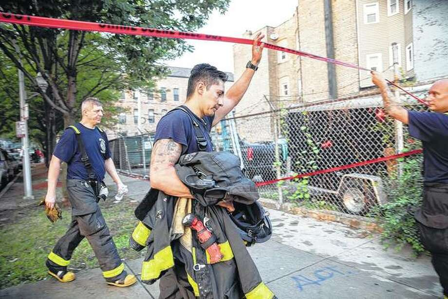 Chicago firefighters walk under tape at the scene of a fire that killed several people including multiple children Sunday. The cause of the blaze hasn't been determined. Photo: Erin Hooley | Chicago Tribune (AP)