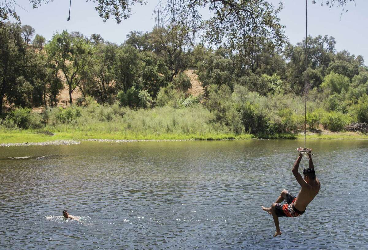 Luis Meza of Waterford, left, and his cousin, Alejandro Vasquez of Chicago, swim in the Tuolumne River in Waterford, California on Friday, August 17, 2018.