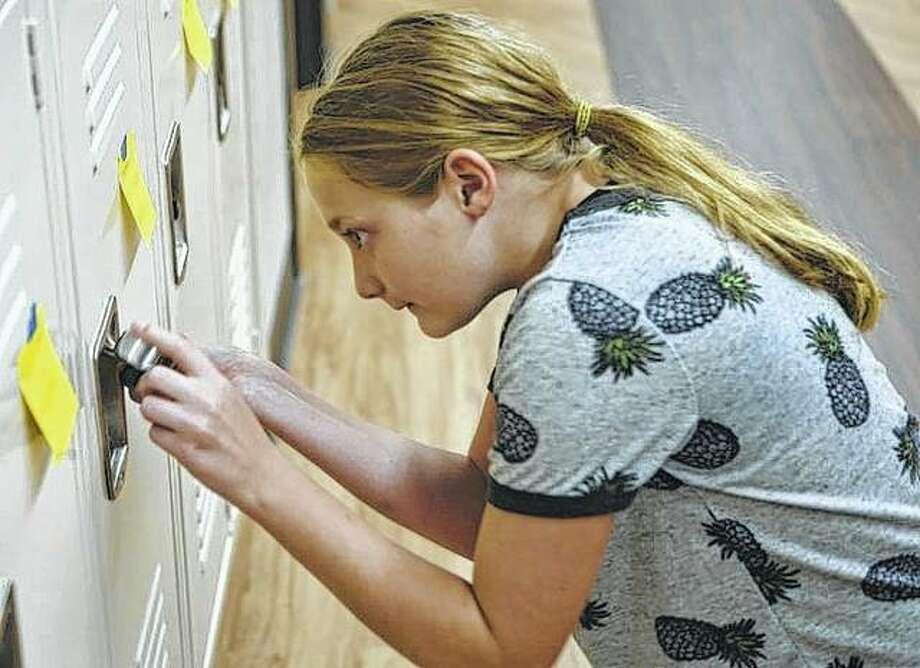 Sixth-grader Samantha Lawson opens her locker at Jacksonville Middle School. Photo: Samantha McDaniel-Ogletree | Journal-Courier
