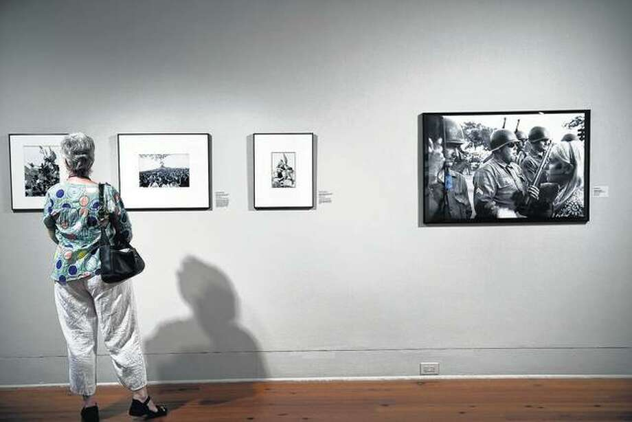 A woman looks at photographs from the 1968 Democratic National Convention at an exhibit in Charlotte, North Carolina. Photo: Brendan Smialowski | AFP (GettyImages)