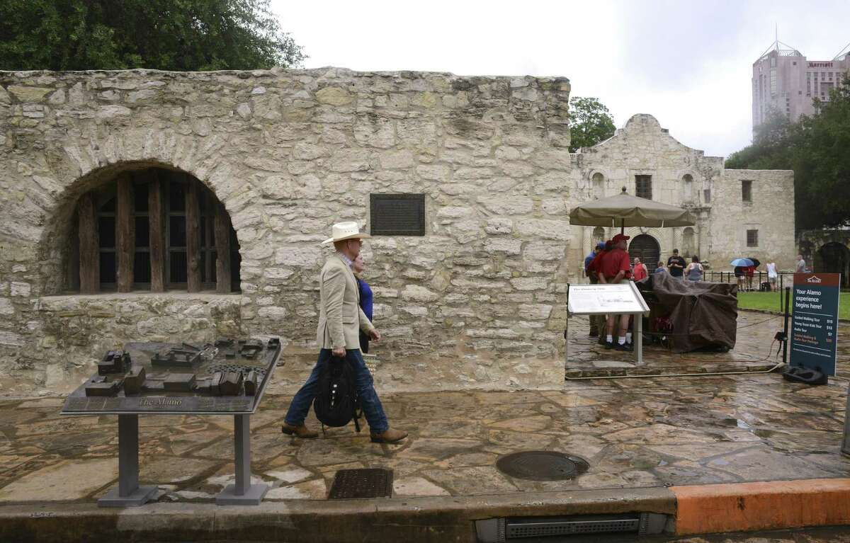 People walk by a bronze panel depicting the evolution of the Alamo from Mission San Antonio de Valero in the 1700s to the military fort known as the Alamo. Several panels have been placed near the Long Barracks and were commissioned by musician Phil Collins, who is a collector of Alamo artifacts.