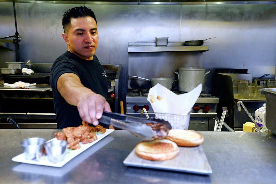 Miguel Juarez plates a lamb burger at The Grill by Arfeen, Smith and Payne.  Photo taken Friday 8/24/18 Ryan Pelham/The Enterprise Photo: Ryan Pelham/The Enterprise / ?2018 The Beaumont Enterprise