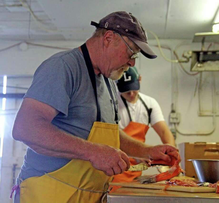 Tod Williams, of the Bay Port Fish Company, filets some fish during a day of work. (Mike Gallagher/Huron Daily Tribune)