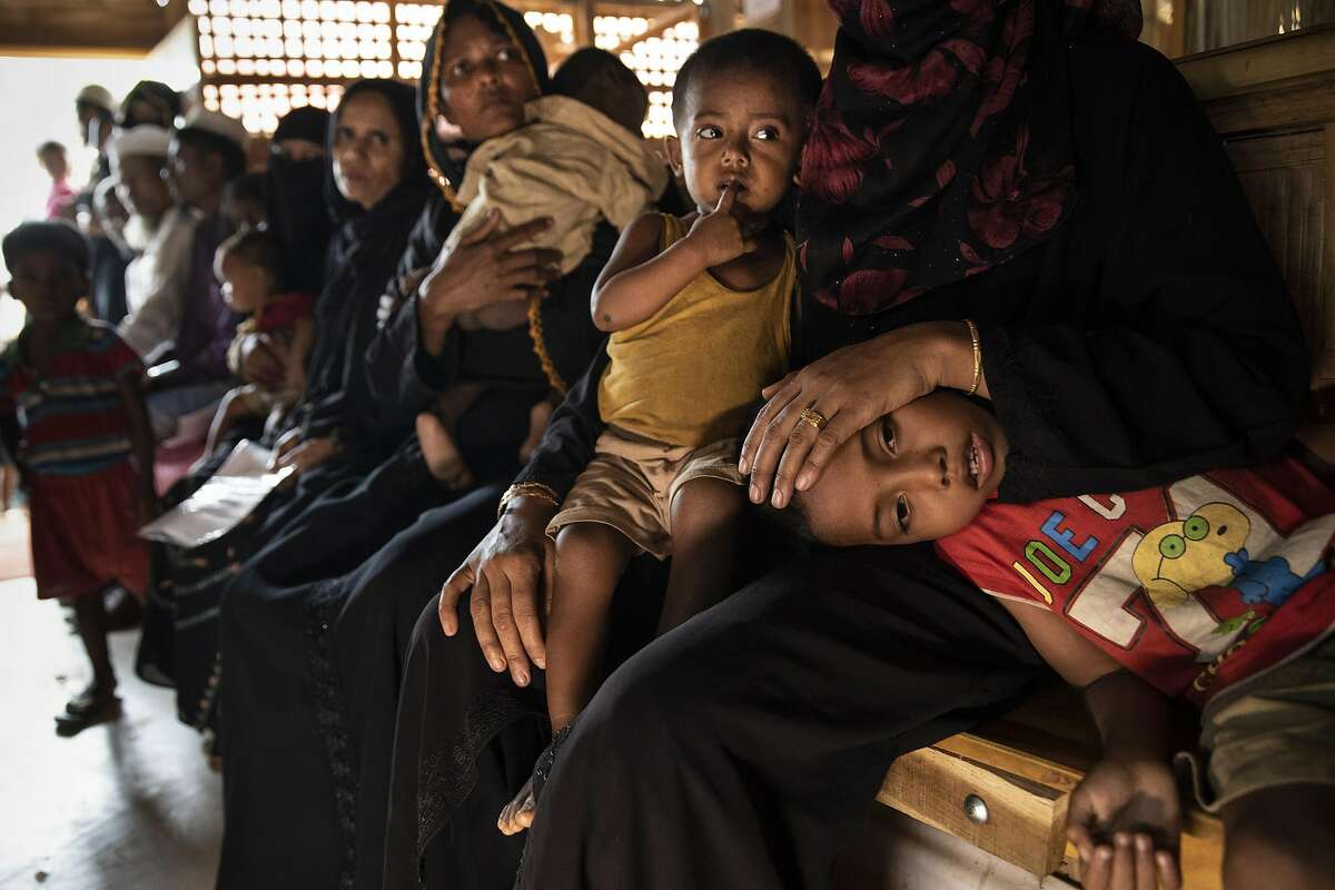 BALUKHALI, BANGLADESH - AUGUST 27: Women and children are seen waiting to be treated in the Médecins Sans Frontières/Doctors Without Borders (MSF) clinic on August 27, 2018 in Balukhali camp, Cox's Bazar, Bangladesh. UN investigators said on Monday that Myanmars army had carried out genocide against the Rohingya in Rakhine state and that its top military figures must be investigated for crimes against minorities across the country. The UN report accused Myanmars military for murders, imprisonments, enforced disappearances, torture, rapes and other forms of sexual violence in Rakhine state, all of which constitute crimes against humanity, as a wave of violence forced more than 720,000 Rohingya to flee into the Coxs Bazar district of Bangladesh one year ago. (Photo by Paula Bronstein/Getty Images)