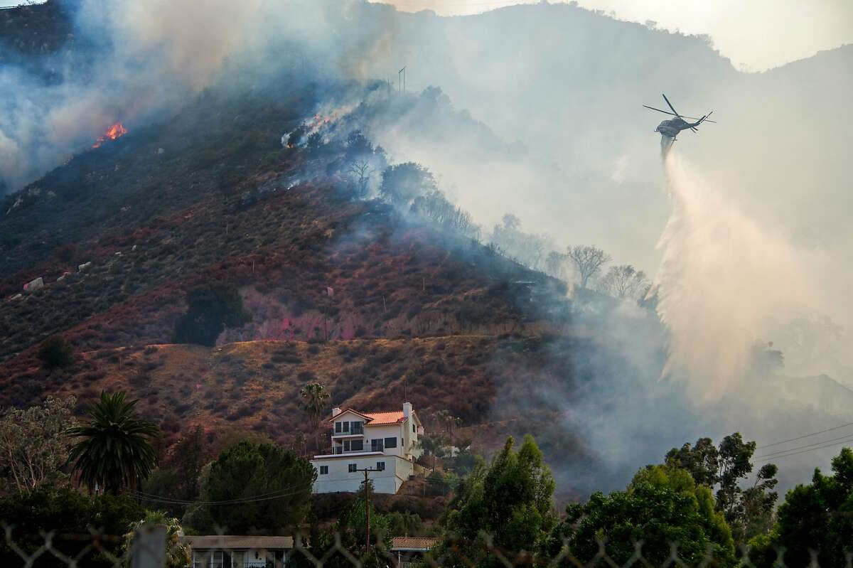 A helicopter drops water to protect a home at the Holy Fire in Lake Elsinore, California, southeast of Los Angeles, on August 10, 2018. - Authorities battling massive wildfires in large swathes of California issued mandatory evacuation orders and health warnings Friday over the worsening air quality as the flames grew ever closer to populated areas. (Photo by Robyn Beck / AFP)ROBYN BECK/AFP/Getty Images