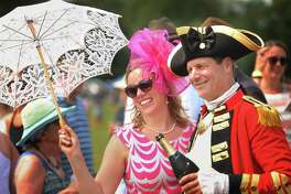 Rachel Bode, of New York City, poses for a photo with Dave Loda, of Bolton, dressed as British Revolutionary War General Sir William Howe, during halftime of a charity polo match at The Fairfield County Hunt Club in Westport, Conn. on Sunday, August 26, 2018. Proceeds from the event benefit the Bridgeport Hospital Foundation's REACH Program.