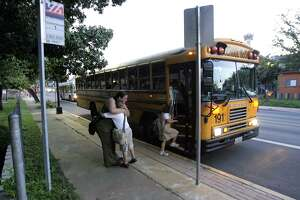 Students board a San Antonio Independent School District bus in this 2007 file photo. The district has contracted with a company to install cameras on its buses to photograph vehicles that fail to stop while the buses are loading or unloading. (WILLIAM LUTHER/STAFF)