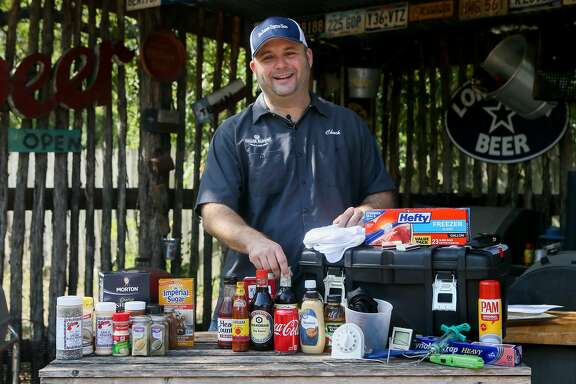 Chuck Blount stands behind an assortment of traditional spices (from left), wet ingredients and gadgets that he suggests to put into your BBQ toolbox at Chuck's Food Shack .