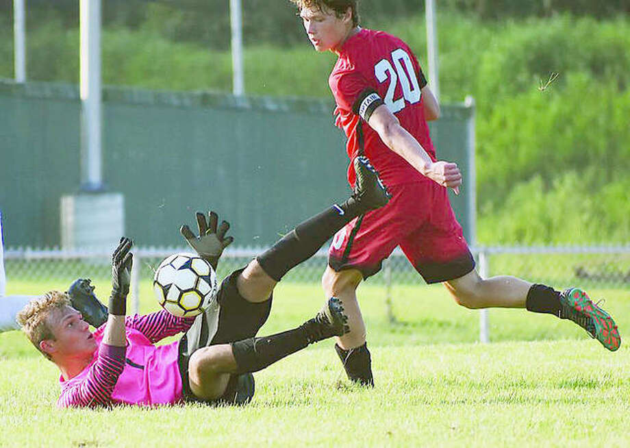 Alton's Joe Morrissey, right, moves in on Edwardsville Tyler Frolick, who makes a diving save in action at the Alton Round-Robin Soccer Tournament at AHS. Photo: Matthew Kamp | For The Telegraph