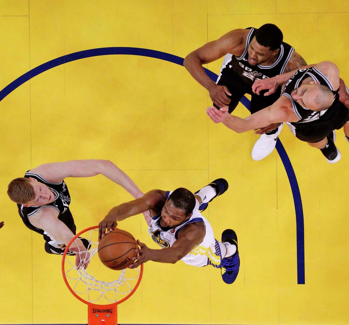 Kevin Durant (35) dunks over Davis Bertans (42) in the second half as the Golden State Warriors played the San Antonio Spurs in Game 5 of the first round of the Western Conference Finals at Oracle Arena in Oakland, Calif., on Tuesday, April 24, 2018. The Warriors won 99-91 to win the series and advance to the second round.