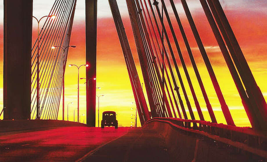 An antique car crosses the Clark Bridge in a vivid sunset. Photo: John Badman | Telegraph File Photo