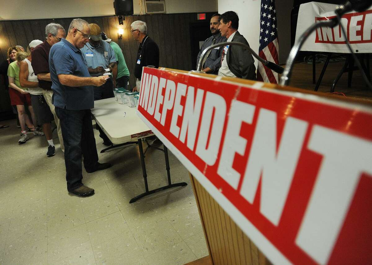 Independent Party voters put their ballots into plastic containers during the party's nominating convention at the Franco-American Social Club in Waterbury on Sunday.