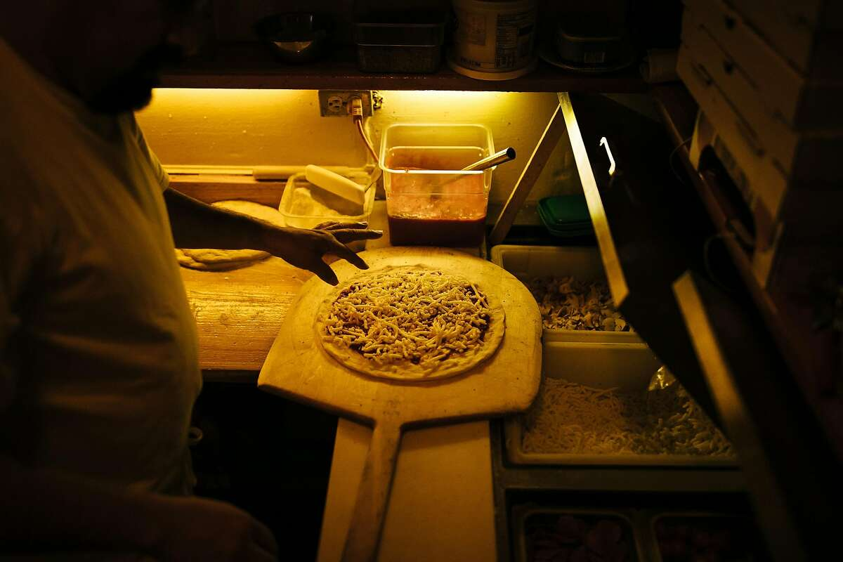 Rigoberto Rojas garnishes the pizzas before putting into the wood-fired brick oven at Tommaso's in San Francisco, Calif. Wednesday, December 6, 2017.