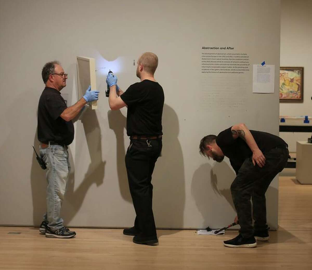 Rico Solinas (left) works on an installation with James Chronister and Kevin Earl Taylor.