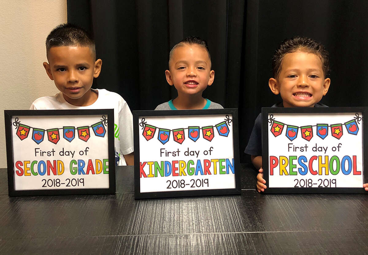 From left, Gilbert, 2nd grade; Austin, kindergarten; and Ayden Casares, preschool, pose for a photo on their first days of school at Meadow Village Elementary on Monday, Aug. 27, 2018.