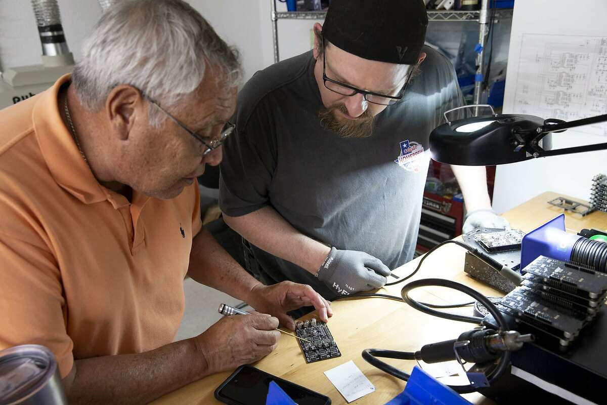 Gerardo Cruces and James Davis troubleshoot a misplaced board of the Ghost Gunner 2, a desktop milling machine designed to construct firearm parts, at the Defense Distributed office in Austin, Texas, on Tuesday, Aug. 7, 2018. Cody Wilson, the founder of Defense Distributed, has been in a long legal dispute regarding his ability to post the instructions to create 3-D printed firearms on his website. (Lynda M. Gonzalez/Austin American-Statesman via AP)