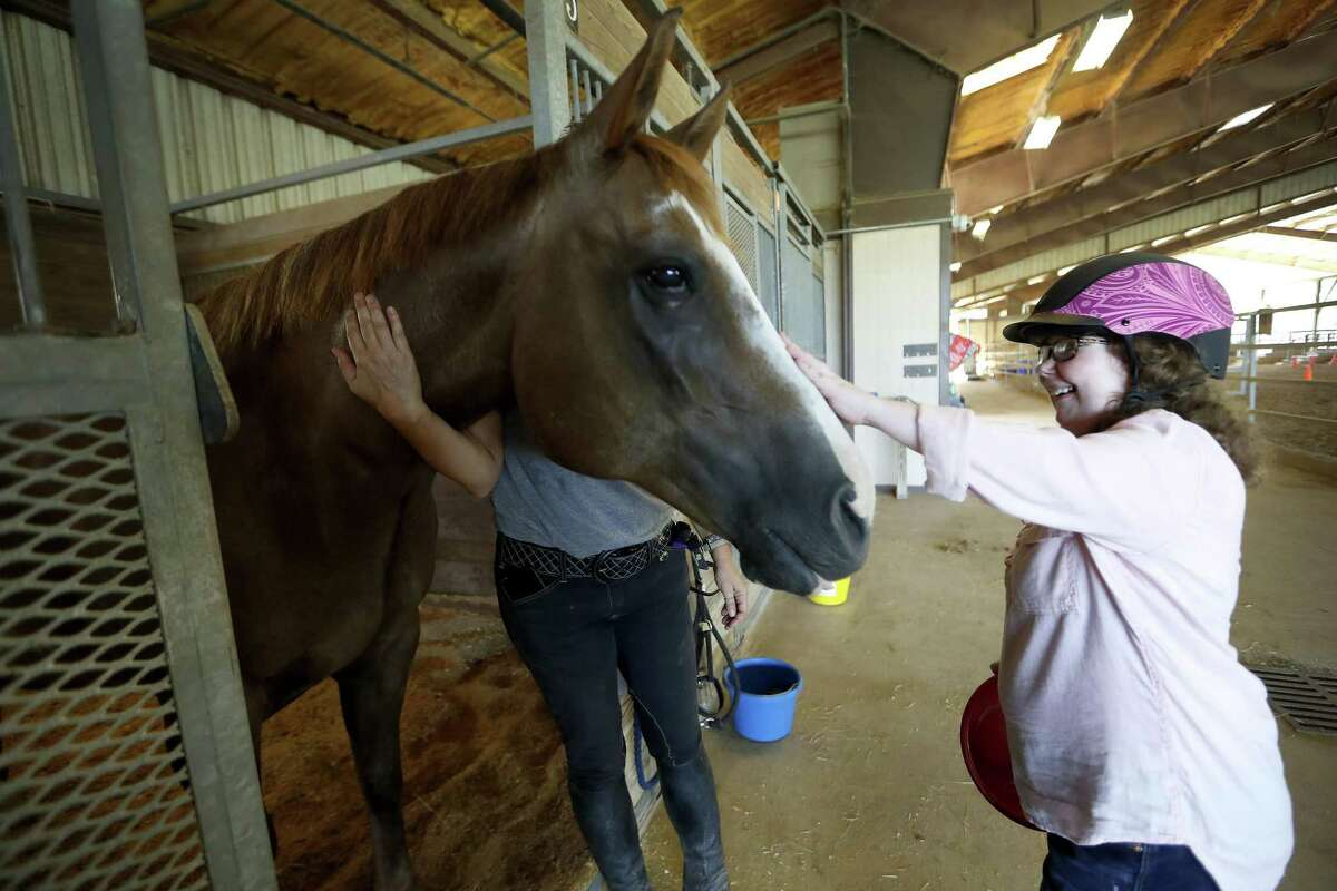 Lauren Hall gives Ernie the horse a treat at SIRE Houston Therapeutic Horsemanship, Tuesday, August 21, 2018, in Richmond. This horseback riding facility in Richmond helps all. Some people go to the facility to heal from a physical injury, and others come to cope with other health issues. The facility even nurses its animals back to health. Nearly a year after a Ernie came to SIRE Houston Therapeutic Horsemanship barely hanging on after Hurricane Harvey ravaged homes and buildings in Houston, and he is now almost fully back to health.