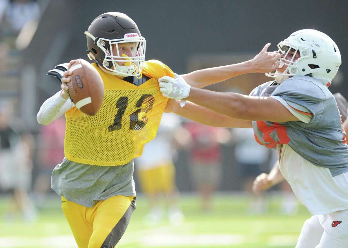 Brunswick quarterback Finn Signer attempts to shed a tackle from Greenwich defensive tackle Jack McBreairty in the high school football preseason scrimmage between Greenwich High School and Brunswick School at Brunswick School in Greenwich, Conn. Monday, Aug. 27, 2018.