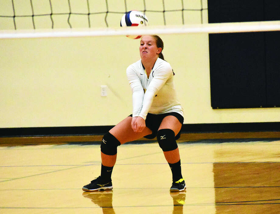 Father McGivney libero Macy Hoppes successfully receives a serve during the first game Mulberry Grove on Monday in Glen Carbon. Photo: Matthew Kamp