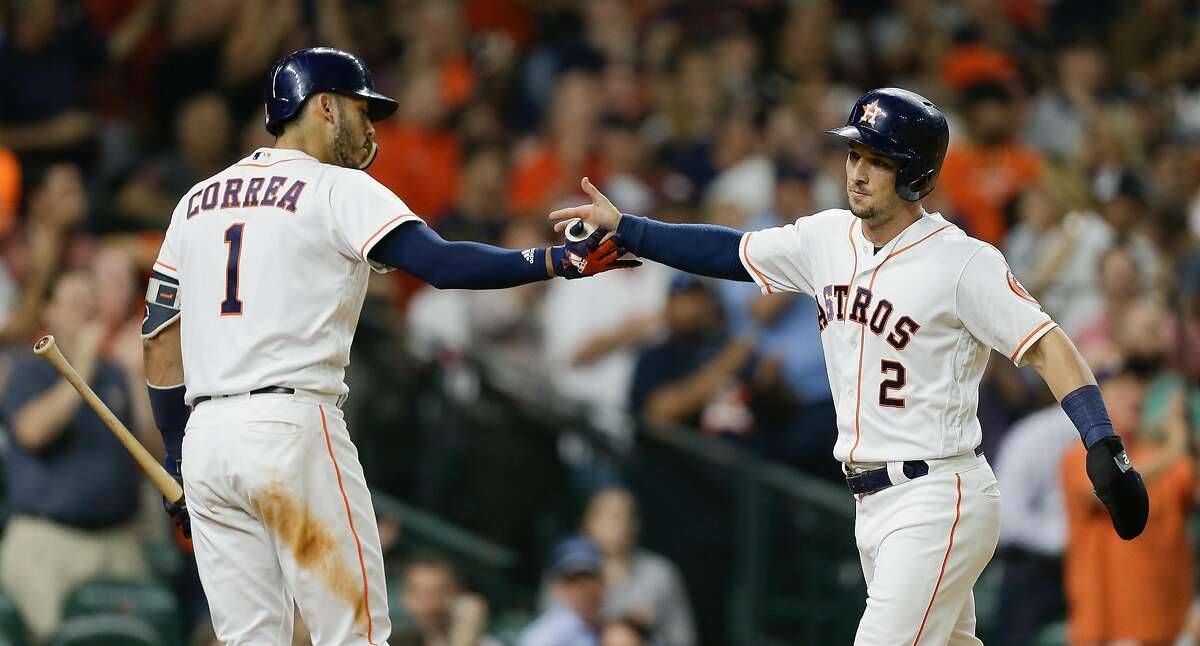 Alex Bregman #2 of the Houston Astros is congratulated by Carlos Correa #1 after scoring in the third inning against the Oakland Athletics at Minute Maid Park on August 27, 2018 in Houston, Texas.
