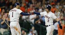 HOUSTON, TX - AUGUST 27:  Alex Bregman #2 of the Houston Astros is congratulated by Carlos Correa #1 after scoring in the third inning against the Oakland Athletics at Minute Maid Park on August 27, 2018 in Houston, Texas.  (Photo by Bob Levey/Getty Images)