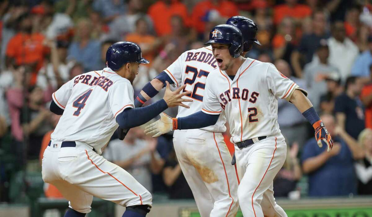 Houston Astros third baseman Alex Bregman (2) is greeted by Houston Astros center fielder George Springer (4) and Josh Reddick (22) after hitting a homer in the 8th inning during an MLB game at Minute Maid Park Monday, Aug. 27, 2018, in Houston.