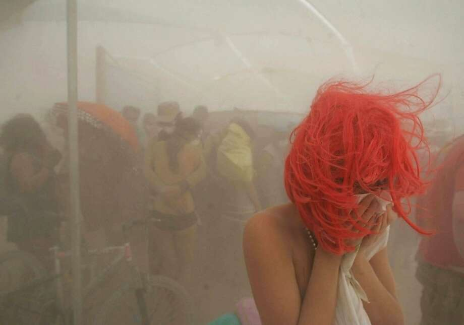 """FILE - In this Aug. 31, 2007 file photo, a woman sits in a shelter during a dust storm on the playa of the Black Rock Desert in Gerlach, Nev., during the Burning Man festival. The #MeToo movement is making its way to Burning Man that begins Aug. 26-Sept. 3, 2018. Organizers are reminding attendees that just because the counterculture festival in the Nevada desert is known for occasional nudity and kinky landmarks like the """"Orgy Dome,"""" it doesn't mean it's a free-for-all when it comes to touching or non-consensual sex. Photo: Brad Horn, Associated Press"""