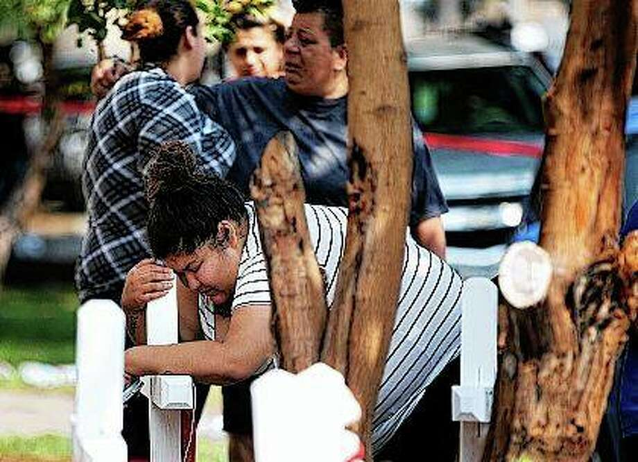 Amber Ayala, who lost siblings in a fatal fire, hugs a wooden cross at the scene in Chicago. Several people were killed in the fire, including six children. Photo: Erin Hooley | Chicago Tribune (AP)
