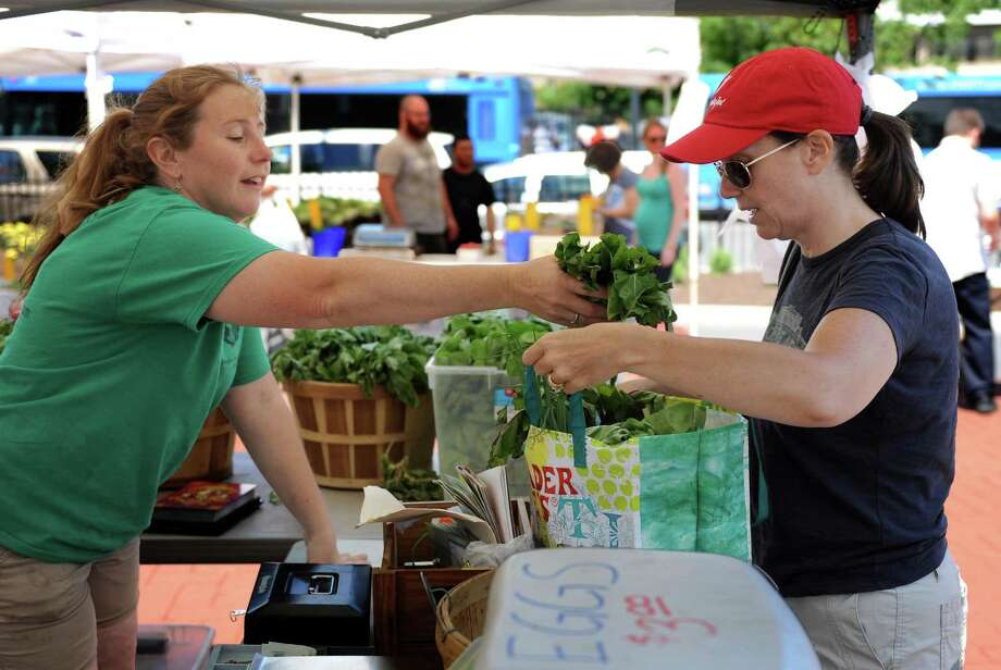 Willow Schulz, left, of New Milford, Conn., sells produce from Clatter Valley Farm at the Danbury Farmer's Market Friday, June 27, 2014.