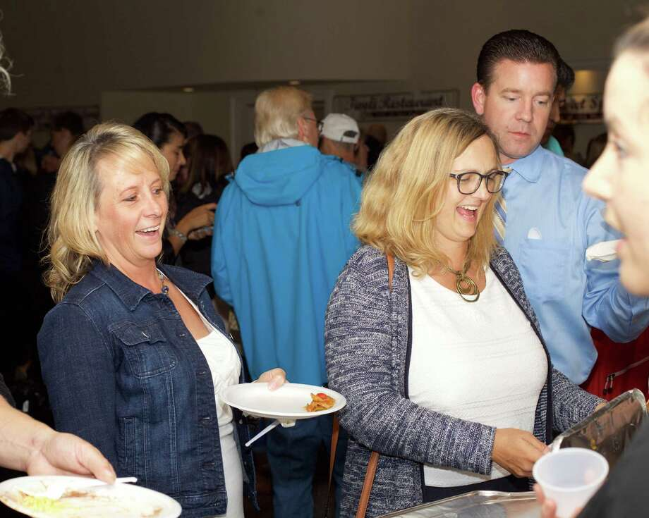 Residents, from left to right, Becky Mulhare, Beth Shields Falder and Scott Mulhare enjoy the samples of food from Zaragoza at 2017 Taste of New Milford. Photo: Trish Haldin / / The News-Times Freelance