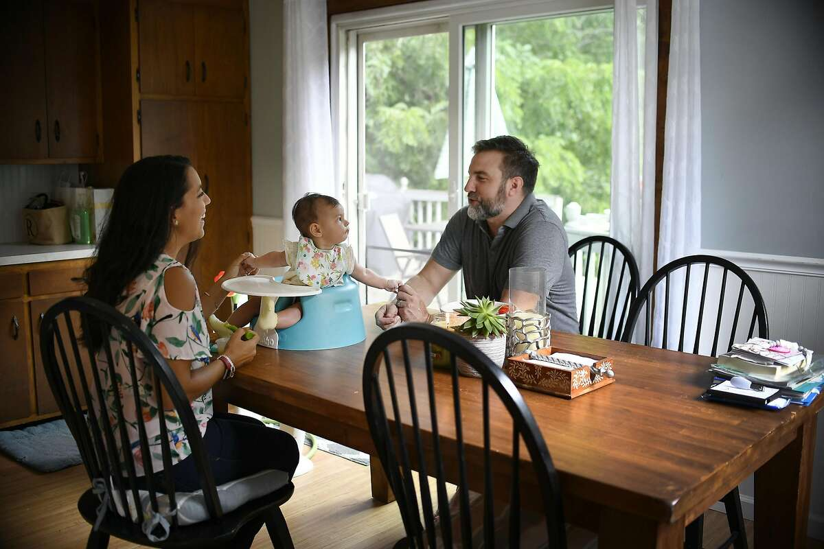 Nicole Roberts and her husband Christopher feed their 5-month old daughter Amelia, at home in North Stonington, Conn., Aug. 20, 2018. Roberts is among a growing number of women who are seeking out fertility apps and wearable devices, like Ava, to help grow their families. (Jessica Hill/The New York Times)