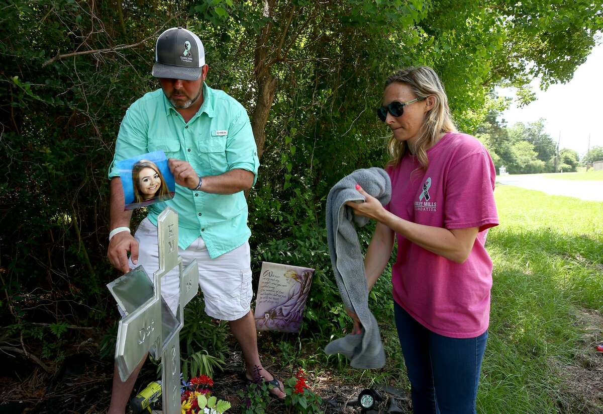 David and Wendy Mills replace Kailee's photograph on a roadside cross at the spot of the October 2017 fatal crash in Spring, Texas.