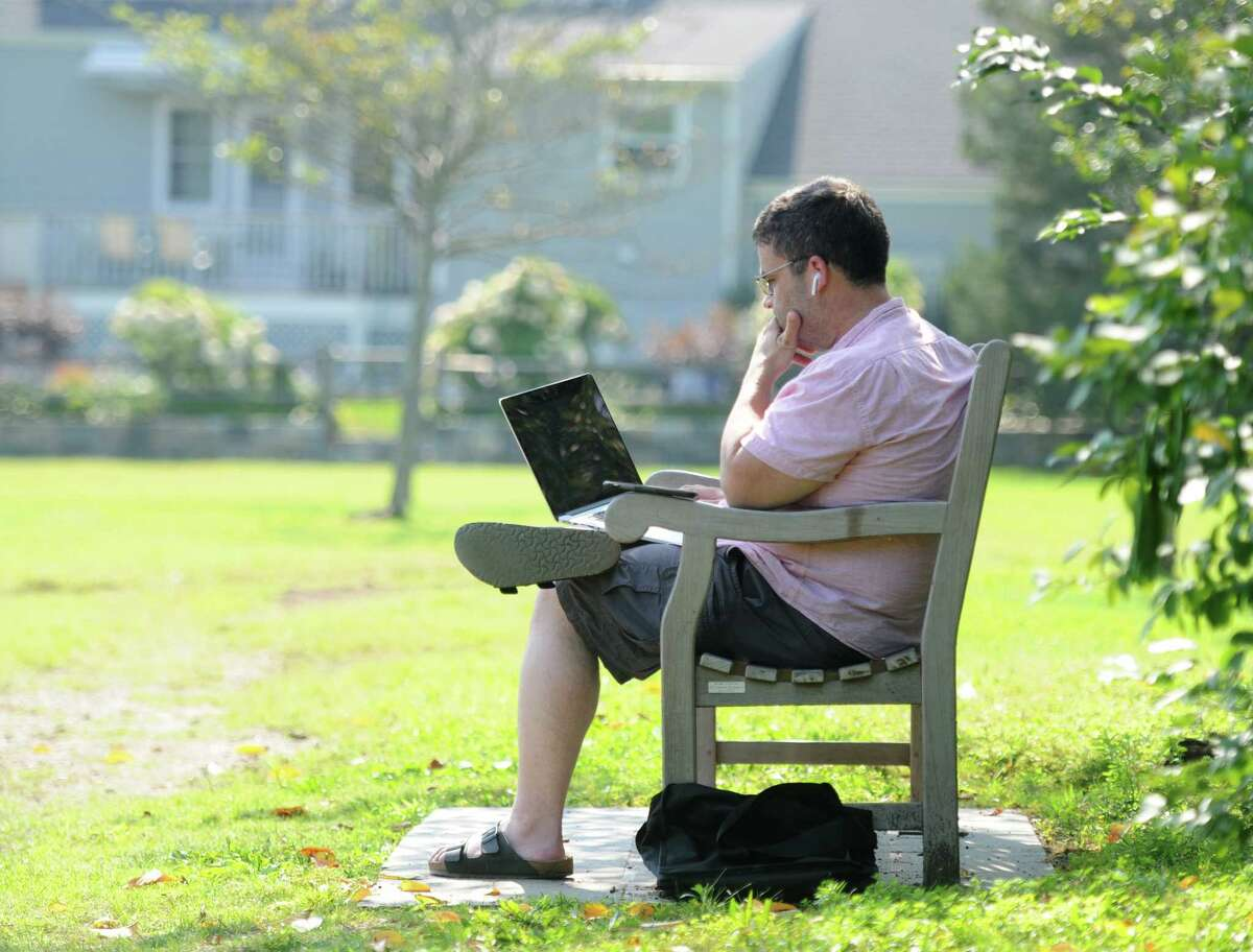 Ryan Hall, of Port Chester, N.Y., gets some work done outside on a hot and humid day by Mill Pond in the Cos Cob section of Greenwich, Conn., in this file photo.