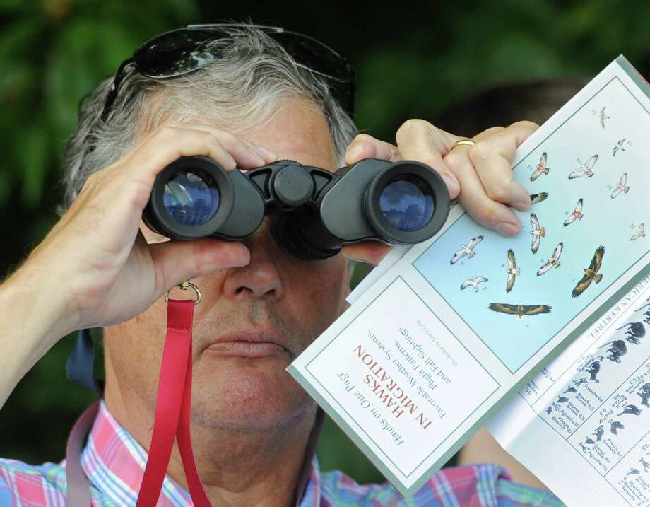 Old Greenwich resident Kees van Meel looks through binoculars in search of migratory raptors during the hawk and raptor identification event at Audubon Greenwich in Greenwich, Conn. Tuesday, Aug. 28, 2018. Folks learned about migratory patterns and how to identify different species of hawks and raptors in flight using binoculars. An average of 20,000 hawks, eagles, falcons and vultures migrate over the Quaker Ridge Hawk Watch held every fall at Greenwich Audubon. The 20th Annual Fall Festival & Hawk Watch will take place Sept. 15 and 16 from 11 a.m. to 4 p.m. at Audubon Greenwich. Photo: Tyler Sizemore, Hearst Connecticut Media / Greenwich Time