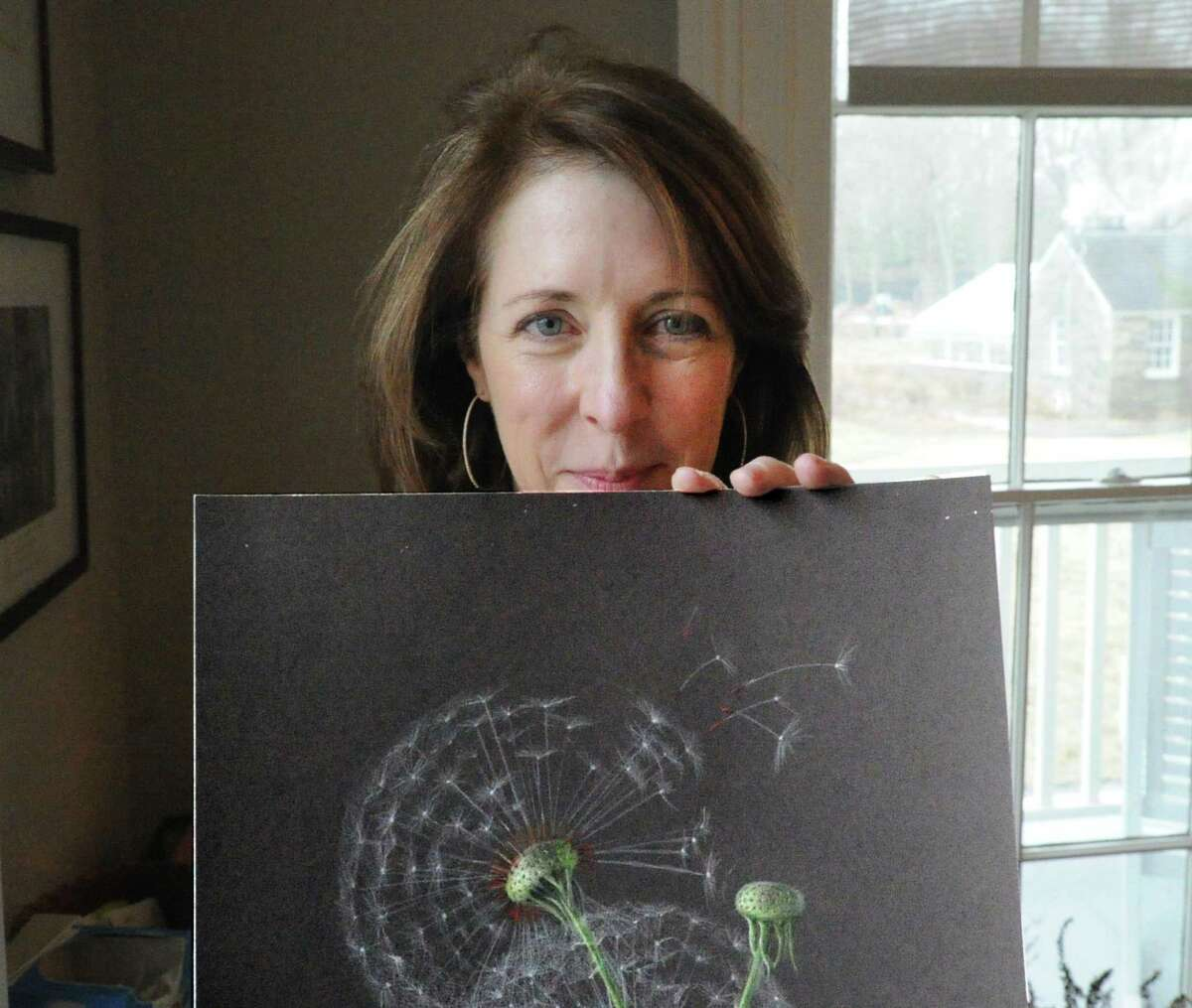 Botanical artist Jeanne Reiner poses with her drawing of a Dandelion seed stem.