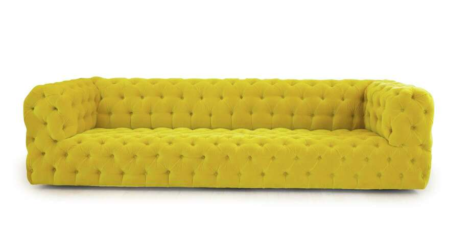 A yellow tufted sofa to anchor a fashionable living room. The Tailored Home in Westport has opened a second shop in Greenwich. Photo: Contributed Photo