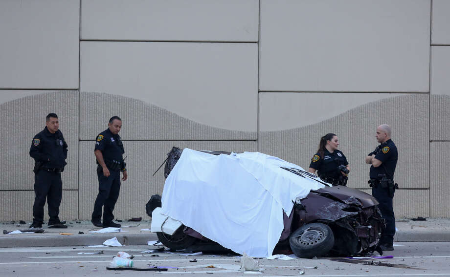 Houston Police officers investigate the scene of a fatal crash on the Gulf Freeway southbound feeder road near El Dorado Boulevard in Friendswood, Texas. A woman and an infant died in the wreck. Photo: Godofredo Vasquez