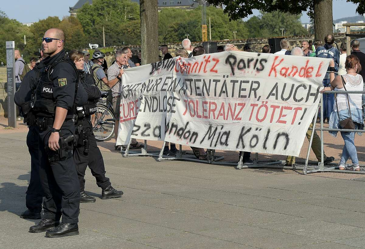 """Police officers guard right wing demonstrators during a far-right demonstration in Dresden, Germany, Tuesday, Aug. 28, 2018 after a man has died and two others were injured in an altercation between several people of """"various nationalities"""" in the eastern German city of Chemnitz on Sunday. (AP Photo/Jens Meyer)"""