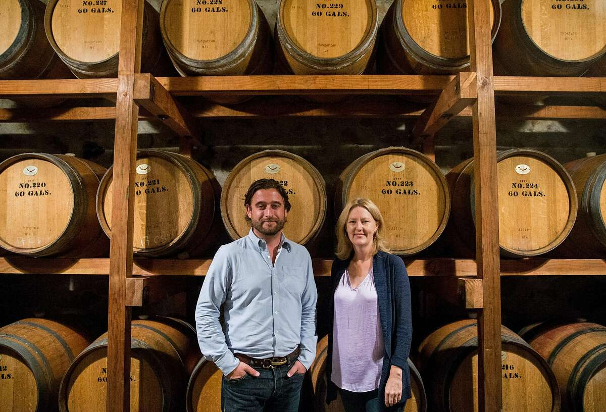 Chris Hall, left, and Sarah McCrea pose for a portrait in front of the original barrels of wine from the 1940s at Stony Hill Vineyard in Calistoga, Calif. Tuesday, Aug. 21, 2018.