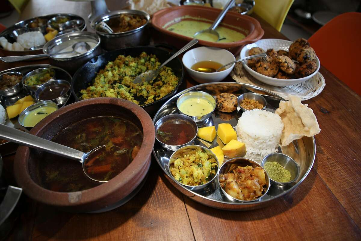 The table is set for a family meal featuring Rasam and other dishes prepared by Vijitha Shyam, at home on Sunday, July 22, 2018, in San Jose, Calif. In the foreground at left is a clay pot with Rasam. At right is a prepared plate ready to eat.