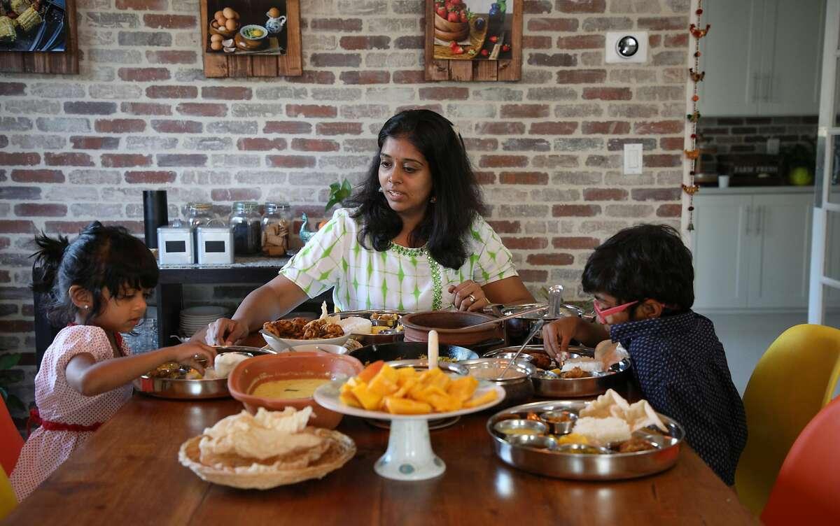 Vijitha Shyam sits down to enjoy a family meal featuring Rasam with her children, Sahana Venba Chander, 4, at left, and Siddharth Vian Chander, 7, at home on Sunday, July 22, 2018, in San Jose, Calif.