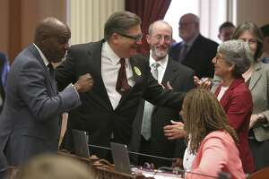 State Sen. Bob Hertzberg, D-Van Nuys, second from left, receives congratulations from fellow Democratic state Senators, Steven Bradford, of Los Angeles, left, Steve Glazer, of Orinda, third from left, and Hannah-Beth Jackson, of Santa Barbara, right, after his bail reform bill was approved by the state Senate, Tuesday, Aug. 21, 2018, in Sacramento, Calif. If signed by Gov. Jerry Brown, it would make California the first state to completely end bail for suspects awaiting trial. (AP Photo/Rich Pedroncelli)