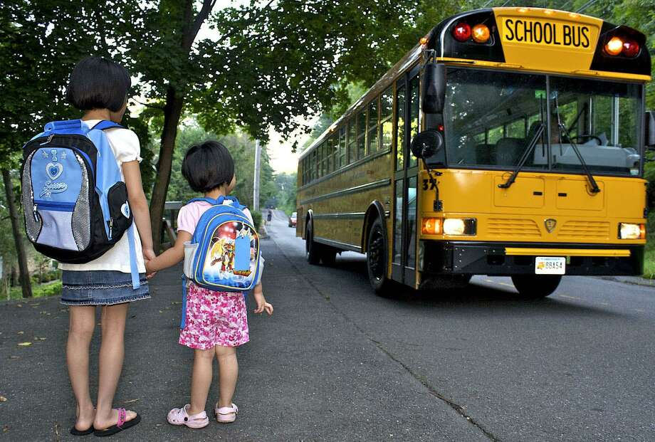 File photo of New Milford students getting the bus on their first day of school. Photo: Trish Haldin / Trish Haldin / The News-Times Freelance